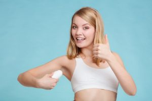 Picture of a woman applying hypoallergenic deodorant under her arms
