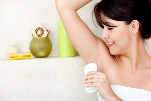 A woman applying a natural deodorant without aluminum